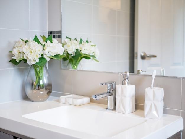 Bacia, sabonete, vaso de flores e escova de dentes branca em um branco limpo e cinza claro b