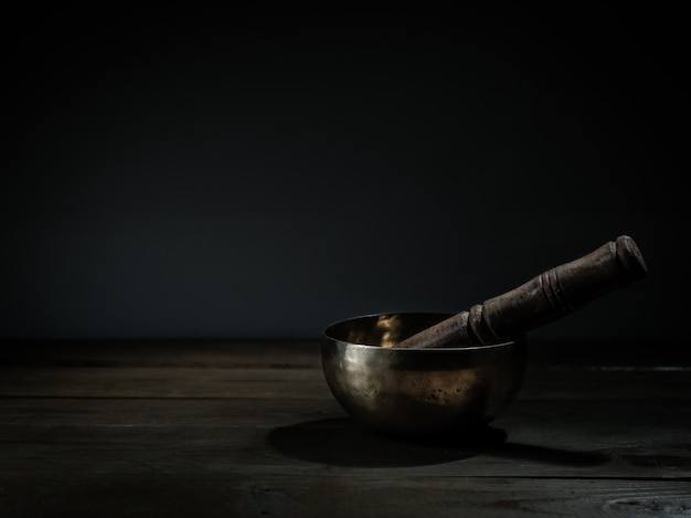 Bacia tibetana velha do canto na base de madeira, fundo preto. terapia musical.