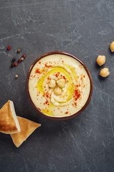 Bacia tradicional do hummus do grão-de-bico com flatbread do grão-de-bico, grãos-de-bico e especiarias no fundo cinzento.