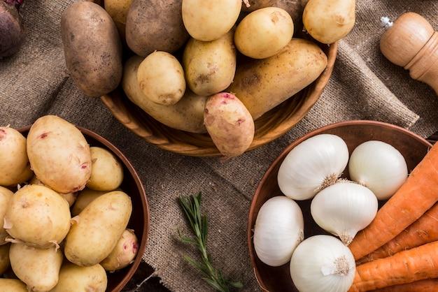 Bacias de madeira com batatas cenoura e alho