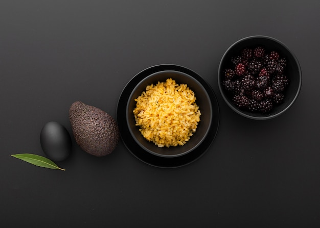 Bacias escuras com arroz e abacate na mesa escura