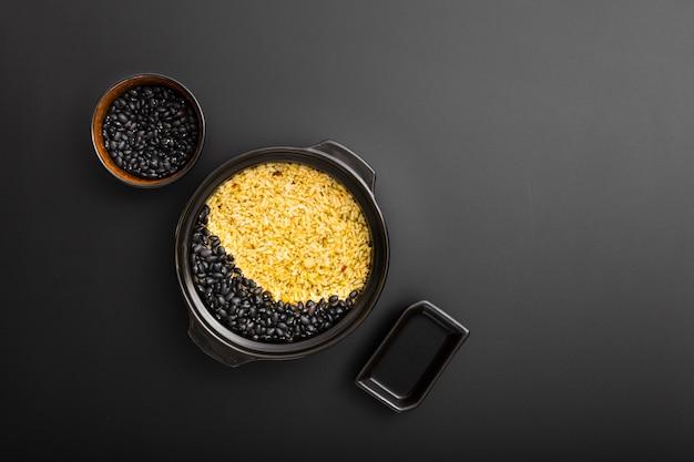 Bacias escuras com arroz e feijão em um fundo escuro