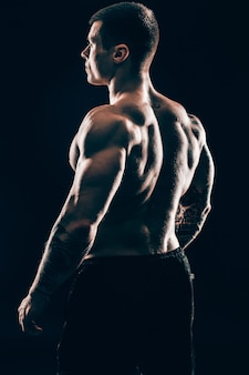 Back view.handsome masculino fisiculturista isolado em fundo preto