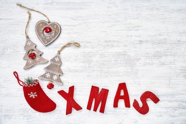 Backgroud de natal com enfeites de natal e letras de madeira vermelhas, formando a palavra xmas. , vista do topo.