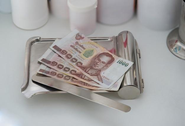 Backnote de dinheiro na bandeja de medicina com pílula de espátula com frasco plástico de droga no fundo no custo de hospital de pagamento de saúde admitir o conceito