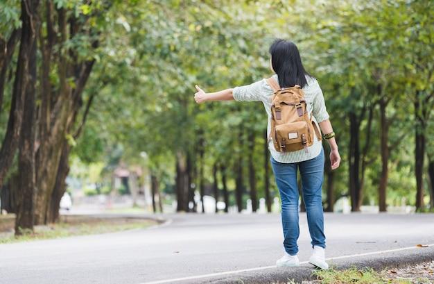 Backpacker asiático da mulher que está na estrada do campo com árvore