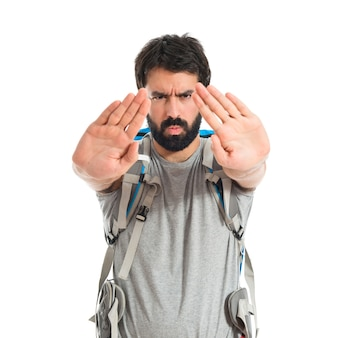 Backpacker fazendo sinal de parada sobre fundo branco