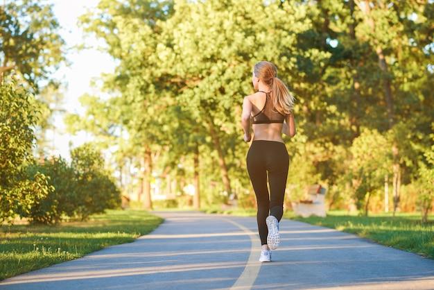 Backview da menina desportiva que corre ao longo da pista no parque da cidade.