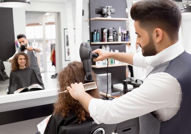 Backview de hairstyler fazendo hairdress para sorrir cliente feminino encaracolado.