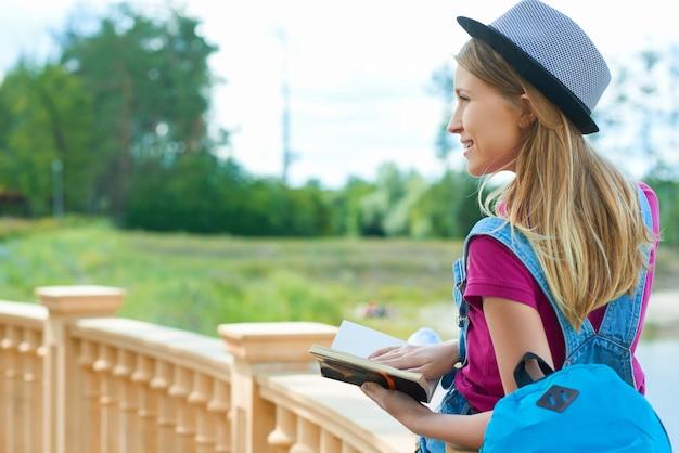 Backview do estudante bonito que senta-se com um livro perto do rio.