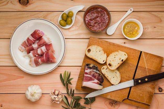 Bacon cru; molho de salsa; azeitonas; torrada; alho; óleo infundido e azeitonas na mesa de madeira