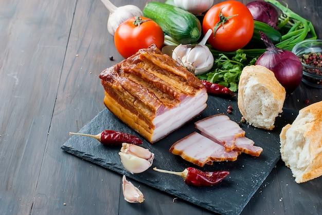 Bacon defumado com baguete e legumes na placa de pedra preta