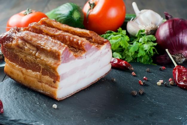 Bacon defumado com legumes na placa de pedra preta