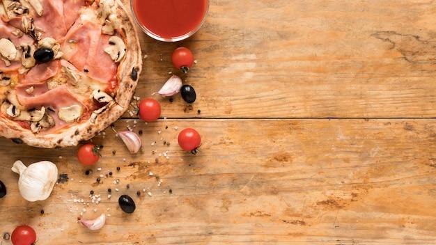 Bacon delicioso; pizza de cogumelos perto de alho; tomate cereja; azeitona preta e tigela de molho de tomate sobre a mesa de madeira