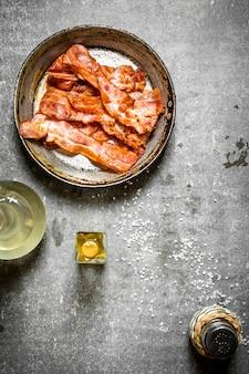 Bacon frito com azeite e sal. sobre um fundo de pedra.