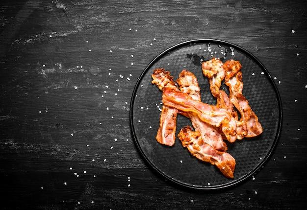 Bacon frito em um prato sobre um fundo preto de madeira