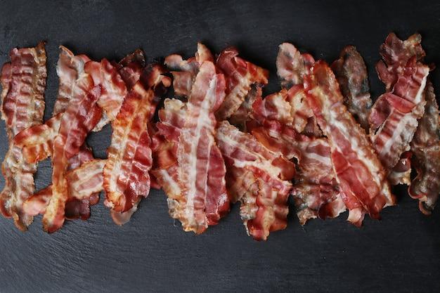 Bacon frito na mesa preta, vista de cima