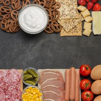 Bacon, linguiça, queijo, vegetais, biscoitos, iogurte de cereais: ingredientes para o café da manhã continental.