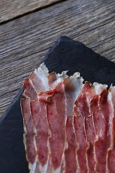 Bacon na placa de pedra preta, vista superior