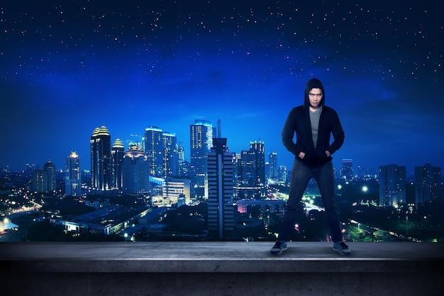 Bad guy de pé no telhado do edifício