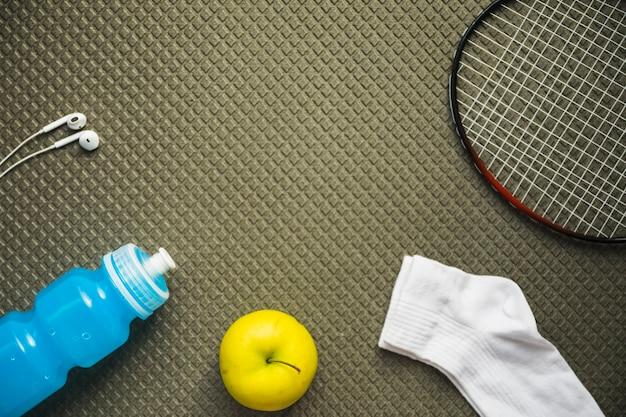 Badminton; maçã; meia; garrafa de água e fone de ouvido no plano de fundo padrão texturizado