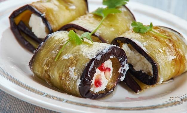 Badrijai nigvzit, comida georgiana, fatias de pasta de nozes cozidas de berinjela, vinagre e temperos é espalhado sobre as fatias de berinjela, que são enroladas.