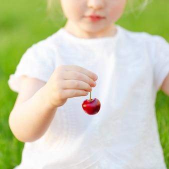 Baga cerejas maduras doces na mão de uma menina bonita.