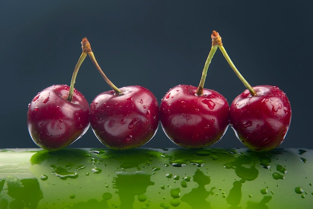 Baga de cereja fresca com gotas de água em uma garrafa verde. comida saudável no café da manhã. frutos da vegetação. sobremesa de fruta