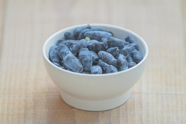 Baga de madressilva azul (amoras, woodbine, woodbind) na chapa branca na mesa de madeira