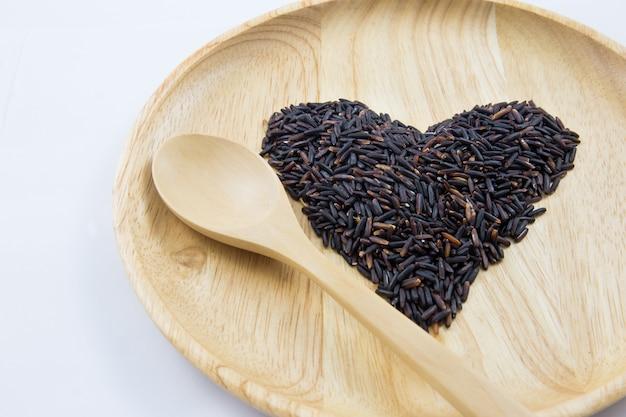 Baga do arroz do coração em umas bacias de madeira com a colher no fundo de madeira. conceito