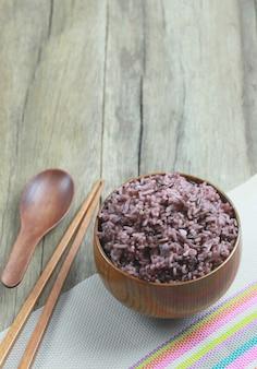 Baga orgânica do arroz no prato de madeira no fundo de madeira.