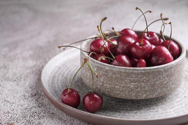 Baga vermelha cereja com gotas de água no prato de cerâmico rústico em fundo de madeira