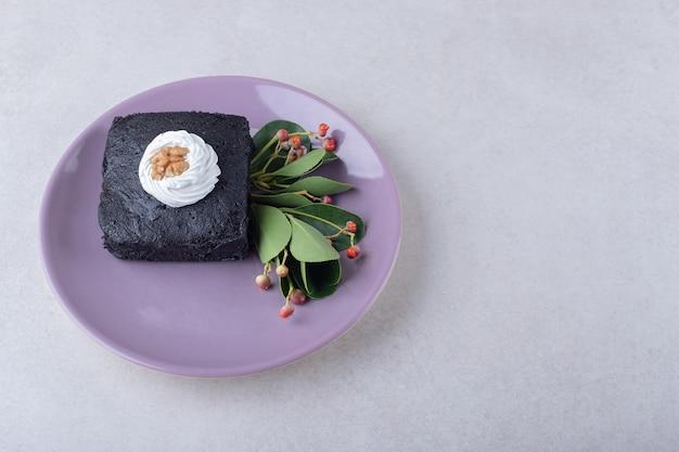 Baga vermelha com bolo de brownies com noz no prato na mesa de mármore.