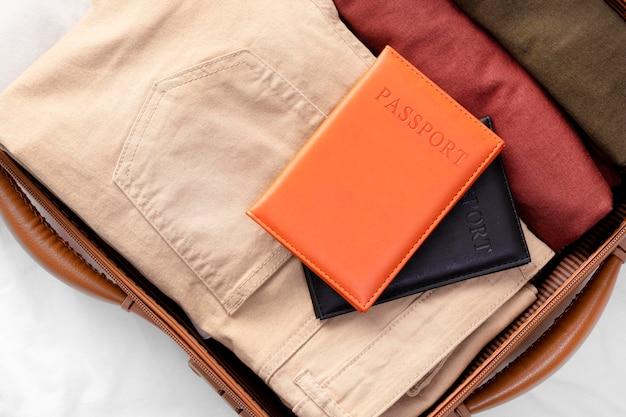 Bagagem aberta com roupa dobrada e passaporte