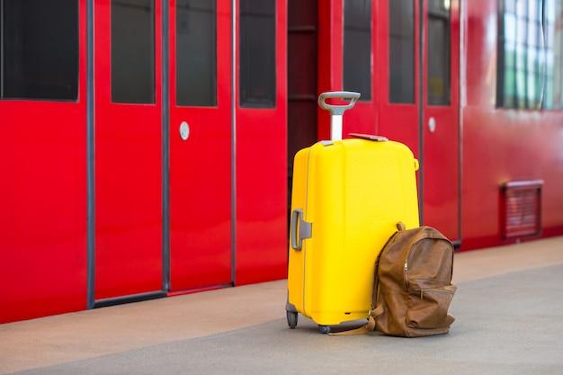 Bagagem amarela com passaportes e mochila marrom na estação de trem