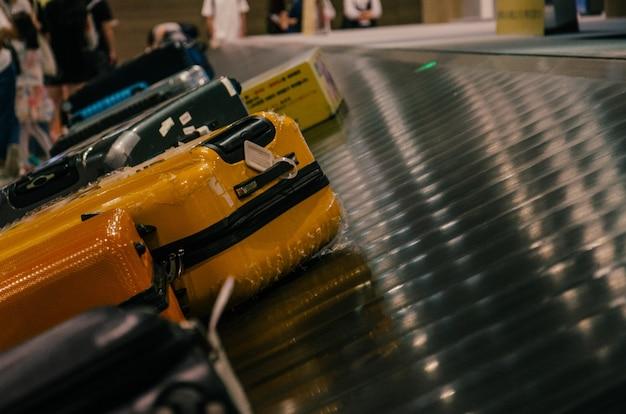 Bagagem amarela na esteira de bagagens do aeroporto
