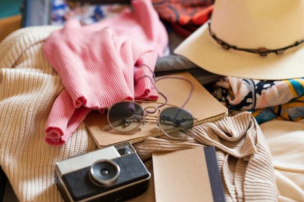 Bagagem com roupas e câmera de alto ângulo