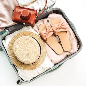 Bagagem de mão com roupas femininas de verão e câmera retro em fundo branco. camada plana, vista superior
