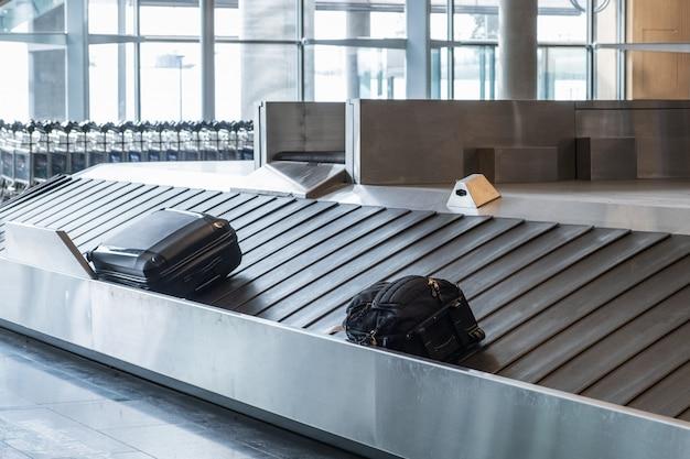 Bagagem de passageiros deslizando sobre trilho na esteira de bagagens