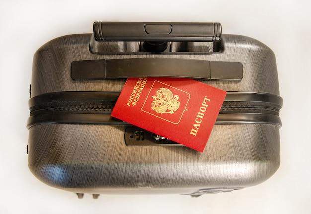 Bagagem de viagem com passaporte, vista de cima. passaporte estrangeiro russo em uma mala preta. conceito: viagens, férias. caixa de plástico com passaporte russo
