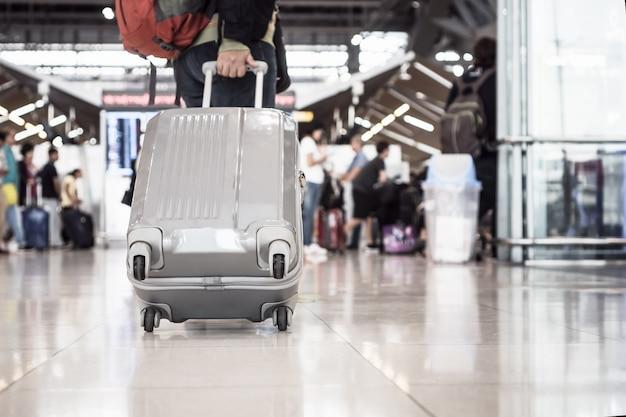 Bagagem de viagem que anda no terminal de aeroporto para o registro.