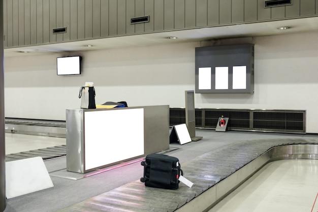 Bagagem deslizando em esteira rolante no aeroporto com outdoor