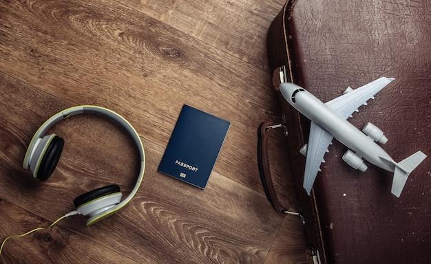 Bagagem velha, fones de ouvido, estatueta de avião, passaporte no chão de madeira