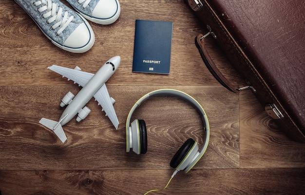 Bagagem velha, fones de ouvido, estatueta de avião, passaporte, tênis no chão de madeira