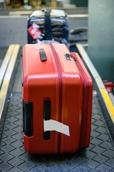 Bagagem vermelha na esteira transportadora para verificação e digitalização no balcão de check-in no aeroporto