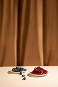 Bagas azuis e sementes de romã suculenta na mesa na frente de fundo marrom