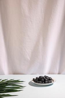 Bagas azuis no prato com folha de palmeira na mesa contra a cortina branca