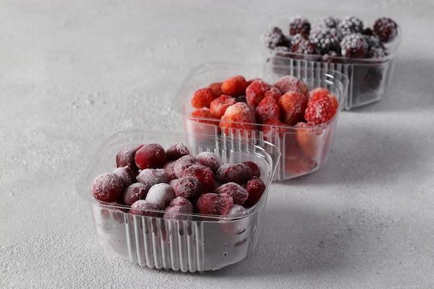 Bagas congeladas, como cerejas, morangos e amoras nas caixas de armazenamento no fundo cinza claro.