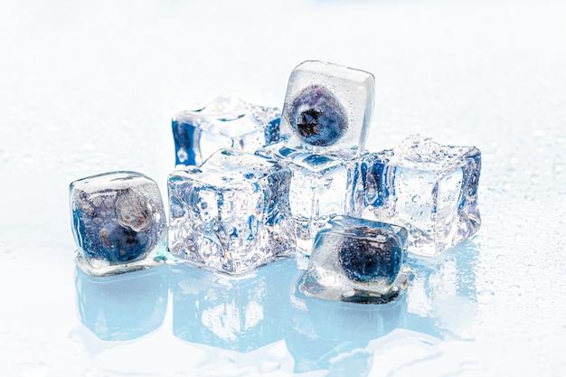 Bagas congeladas em cubos de gelo na rosa