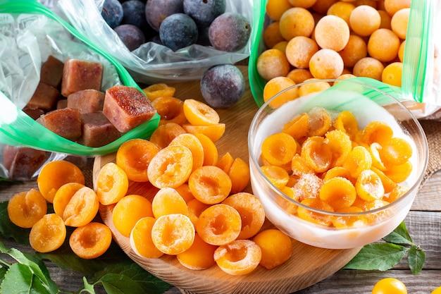 Bagas congeladas na mesa. ameixas congeladas, ameixas cereja em sacos e recipientes. armazenamento de alimentos
